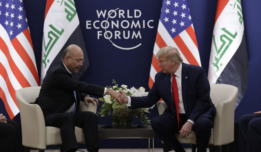 US President Donald Trump, right, shakes hands with his Iraqi counterpart Barham Salih at the World Economic Forum in Davos, Switzerland, Wednesday, Jan. 22, 2020. Trump's two-day stay in Davos is a test of his ability to balance anger over being impeached with a desire to project leadership on the world stage. (AP Photo/Evan Vucci)