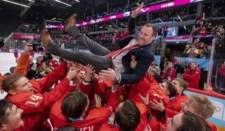 In this photo provided by the IOC, Russia team coach Vladimir Filatov is lifted as his team celebrates defeating the USA in the final of the men's ice hockey competition at the 2020 Winter Youth Olympic Games in Lausanne, Switzerland, Wednesday, Jan. 22, 2020. (Joel Marklund for OIS via AP)