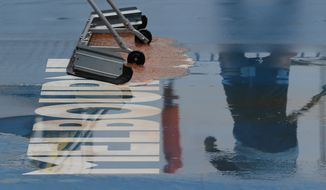 Ground staff clear and dry the outside courts after rain delayed play during a second round singles match at the Australian Open tennis championship in Melbourne, Australia, Thursday, Jan. 23, 2020. (AP Photo/Andy Wong)