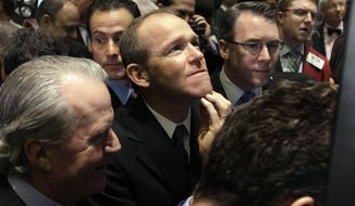 FILE - In this Jan. 26, 2011 file photo, Nielsen Company CEO David Calhoun, center, watches progress as he waits for the company's IPO to begin trading, on the floor of the New York Stock Exchange. Calhoun, Boeing's new CEO, said Wednesday, Jan. 22, 2020, that production of the 737 Max will resume this spring, months before the company expects federal regulators to certify the grounded plane to fly again. (AP Photo/Richard Drew, File)