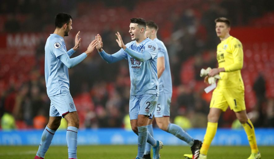 Burnley's Dwight McNeil, left, and Matthew Lowton celebrate at the end of the Premier League match at Old Trafford, Manchester Wednesday January 22, 2020.   (Martin Rickett/PA via AP)