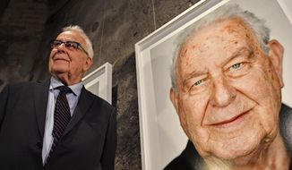 Holocaust survivor Naftali Furst stands next to his portrait during the opening of the exhibition 'Survivors - Faces of Life after the Holocaust' at the former coal mine Zollverein in Essen, Germany, Tuesday, Jan. 21, 2020. The industrial world heritage landmark Zollverein shows 75 years after the liberation of the Nazi death camp Auschwitz-Birkenau, 75 portraits of Jewish survivors, photographed in Israel by German artist Martin Schoeller. (AP Photo/Martin Meissner)