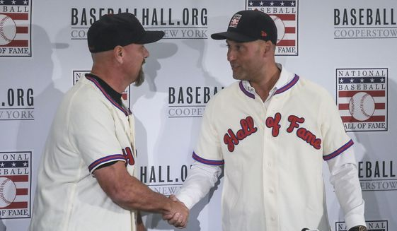 Colorado Rockies outfielder Larry Walker, left, and New York Yankees shortstop Derek Jeter shake hands after receiving their Baseball Hall of Fame jersey and cap, Wednesday Jan. 22, 2020, during a news conference in New York. (AP Photo/Bebeto Matthews)