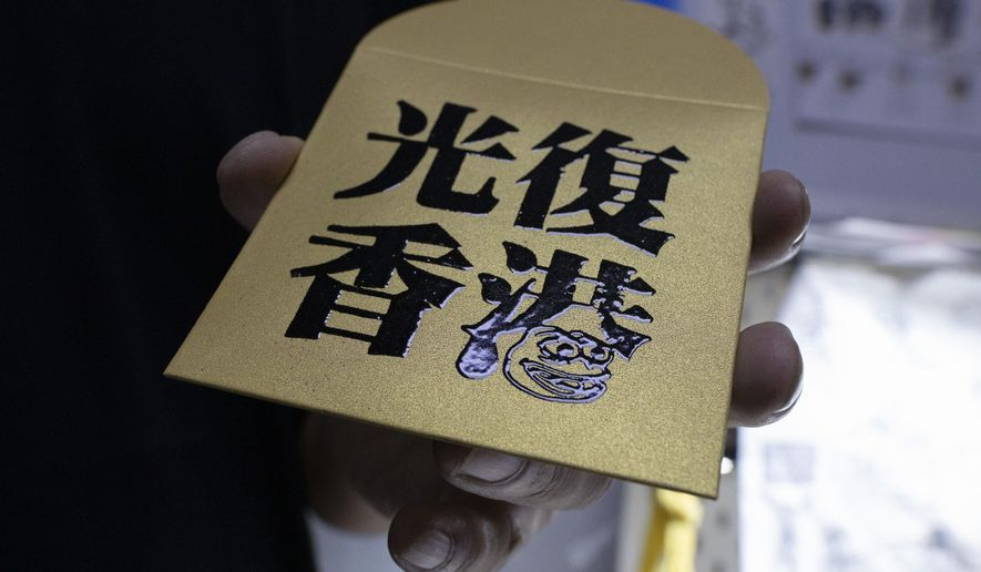 """In this Saturday, Jan. 18, 2020, photo, Jason Kwan holds up a red packet with the words """"Liberate Hong Kong"""" as he poses for a photo in his workshop in Hong Kong. Sharing red packets stuffed with cash is an important Lunar New Year tradition. Printed messages generally convey wishes for prosperity and happiness, but Hong Kong's anti-government protests are putting a new spin on the tradition. Artist Kwan is designing politically themed rubber stamps so senders can add political messages. (AP Photo/Ng Han Guan)"""
