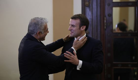 French President Emmanuel Macron, right, meets with Yair Lapid, left, in Jerusalem on Wednesday, Jan. 22, 2020.  Dozens of world leaders have descended upon Jerusalem for the largest-ever gathering focused on commemorating the Holocaust and combating modern-day anti-Semitism. (Abir Sultan/Pool Photo via AP)