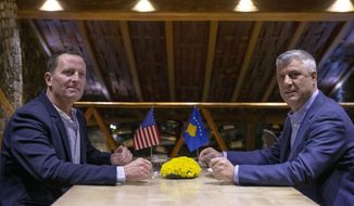 Kosovo's President Hashim Thaci, right, and  U.S. ambassador to Germany Richard Grenell pose for a photograph, in Kosovo capital Pristina, Wednesday, Jan. 22, 2019. Grenell, who is U.S. President Donald Trump's special envoy for Serbia and Kosovo visited Kosovo in an effort to urge both countries to resume negotiations and reach a final reconciliation agreement. (AP Photo/Visar Kryeziu)