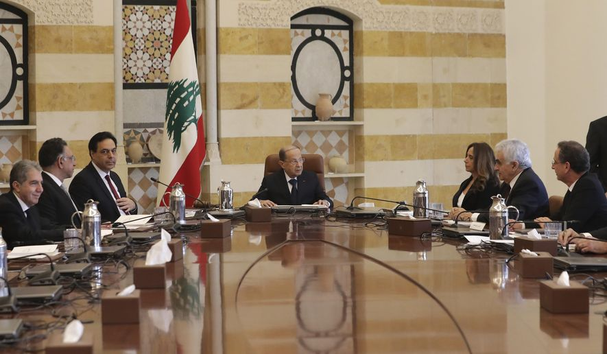President Michel Aoun, center, speaks with Deputy Prime Minister and Minister of Defense Zeina Akr, center, right as Prime Minister Hassan Diab, center left, looks on during the cabinet meeting at the presidential palace in Baabda, east of Beirut, Lebanon Wednesday, Jan. 22, 2020. A new Cabinet has been announced last night in crisis-hit Lebanon, breaking a months-long impasse amid mass protests against the country's ruling elite. (AP Photo/Hassan Ammar)