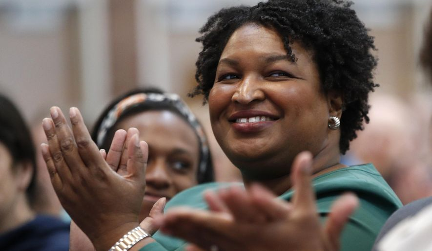 Stacey Abrams, a Georgia Democrat who has launched a multimillion-dollar effort to combat voter suppression, applauds a dignitary at the University of New England, Wednesday, Jan. 22, 2020 in Portland, Maine. Abrams was a Georgia state legislator who became the first black woman to win a major party gubernatorial nomination in U.S. history. (AP Photo/Robert F. Bukaty)