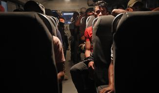 Honduran migrants who have agreed to be returned home, sit on a bus provided by the Guatemalan government in Tecun Uman, Guatemala, Tuesday, Jan. 21, 2020. Hundreds of Central American migrants who entered southern Mexico in recent days have either been pushed back into Guatemala by Mexican troops, shipped to detention centers or returned to Honduras, officials said Tuesday. An unknown number slipped past Mexican authorities and continued north. (AP Photo/Moises Castillo)