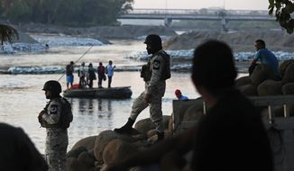 Mexican National Guards stand watch over the the Suchiate River where locals transport food and people between Mexico and Guatemala, as they stand near Ciudad Hidalgo, Mexico, Wednesday, Jan. 22, 2020, a location popular for migrants to cross from Guatemala to Mexico. Mexico announced last June that it was deploying the newly formed National Guard to assist in immigration enforcement to avoid tariffs that Trump threatened on Mexican imports. (AP Photo/Marco Ugarte)