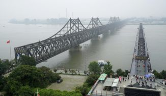 FILE - In this Sept. 9, 2017, file photo, visitors walk across the Yalu River Broken Bridge, right, next to the Friendship Bridge connecting China and North Korea in Dandong in northeastern China's Liaoning province. North Korea banned foreign tourists to guard against the spread of a new virus from China, a tour operator said. The temporary closing of the North Korean border would begin Wednesday, Jan. 22, 2020. (AP Photo/Emily Wang, File)