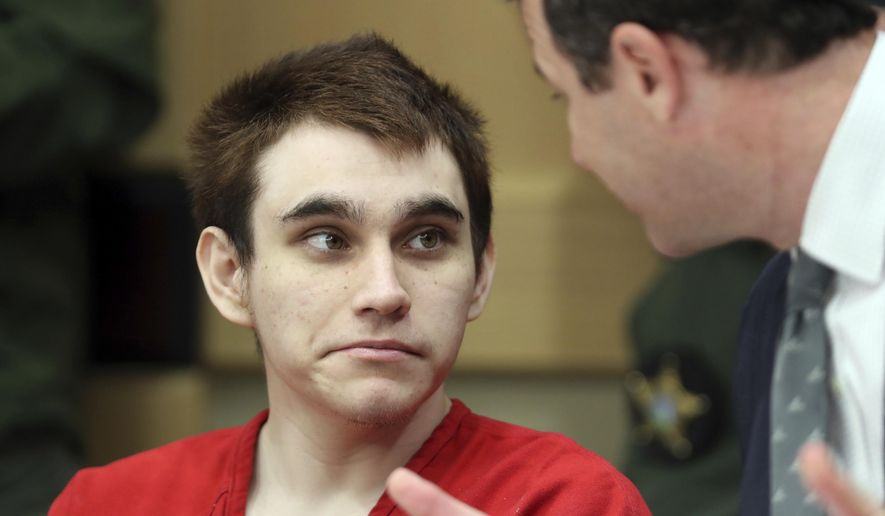 Florida school shooting defendant Nikolas Cruz speaks with one of his defense attorneys, Gabe Ermine, before a hearing at the Broward County Courthouse in Fort Lauderdale, Fla., Wednesday, Jan. 22, 2020. (Amy Beth Bennett/South Florida Sun-Sentinel via AP, Pool)