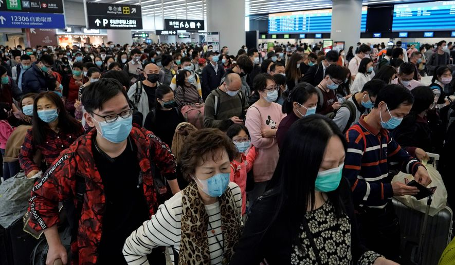 Passengers wear protective face masks at the departure hall of the high speed train station in Hong Kong on Thursday. China closed off a city of more than 11 million people Thursday, halting transportation and warning against public gatherings. (ASSOCIATED PRESS)