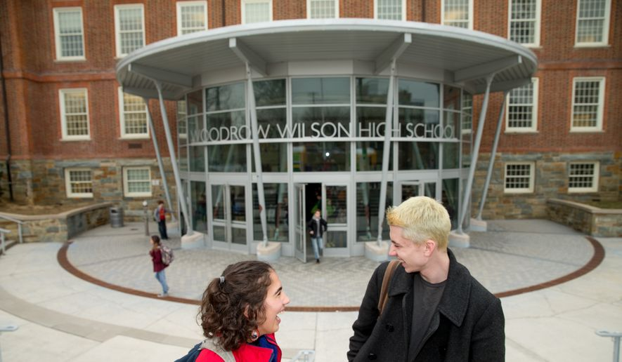 High School juniors Brian Keyes and Isabel Suarez, both 16, pose for a photograph in front of Woodrow Wilson High School in Washington, Thursday, March 3, 2016, after recently taking the new SAT exam. (AP Photo/Andrew Harnik) **FILE**