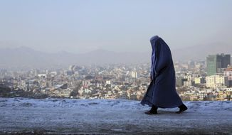 A woman walks on a street overlooking the city of Kabul, Afghanistan, Thursday, Jan. 23, 2020. (AP Photo/Tamana Sarwary) ** FILE **