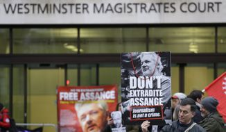 Demonstrators supporting Julian Assange hold banners outside Westminster Magistrates Court in London, Thursday, Jan. 23, 2020. Assange is scheduled to be presented before the court in Westminster by videolink, for a case management hearing ahead of his full extradition trial which begins on Feb. 24. at Woolwich Crown Court. (AP Photo/Kirsty Wigglesworth)