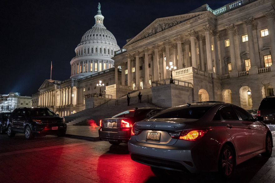 Official's vehicles wait outside the Senate as lawmakers work late Thursday, Jan. 23, 2020, on arguments in the impeachment trial of President Donald Trump on charges of abuse of power and obstruction of Congress, in Washington. (AP Photo/J. Scott Applewhite)
