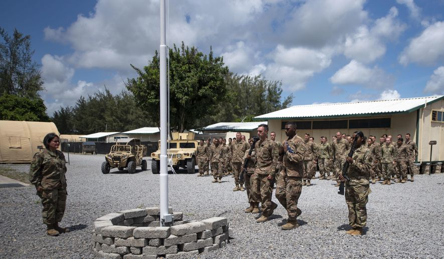 In this Aug. 26, 2019, file photo released by the U.S. Air Force, airmen from the 475th Expeditionary Air Base Squadron conduct a flag-raising ceremony, signifying the change from tactical to enduring operations, at Camp Simba, Manda Bay, Kenya. (Staff Sgt. Lexie West/U.S. Air Force via AP) ** FILE **