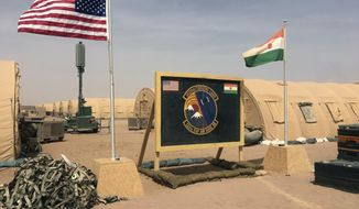 In this photo taken Monday, April 16, 2018, a U.S. and Niger flag are raised side by side at the base camp for air forces and other personnel supporting the construction of Niger Air Base 201 in Agadez, Niger. (AP Photo/Carley Petesch, File)