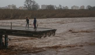 Two people take snapshots atop of a collapsed bridge in Malgrat, near Barcelona, Spain, Wednesday, Jan. 22, 2020. Since Sunday the storm has hit mostly eastern areas of Spain with hail, heavy snow and high winds, while huge waves smashed into towns on the Mediterranean coast and nearby islands of Mallorca and Menorca. (AP Photo/Joan Mateu)