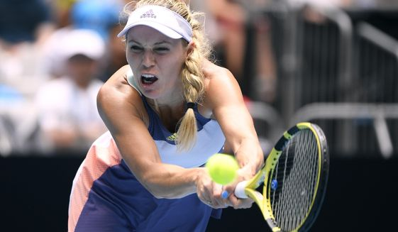 Denmark's Caroline Wozniacki makes a backhand return to Tunisia's Ons Jabeur in their third round singles match at the Australian Open tennis championship in Melbourne, Australia, Friday, Jan. 24, 2020. (AP Photo/Andy Brownbill)