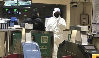 A security officer wears a hazardous materials suit at a subway station in Beijing, Friday, Jan. 24, 2020. China moved to lock down at least three cities with a combined population of more than 18 million in an unprecedented effort to contain the deadly new virus that has sickened hundreds of people and spread to other parts of the world during the busy Lunar New Year holiday. (AP Photo/Yanan Wang)