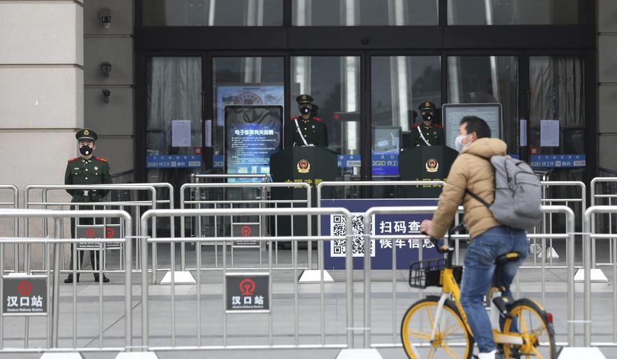 A man rides his bicycle past the closed Hankou Railway Station in Wuhan in central China's Hubei Province, Thursday, Jan. 23, 2020. Overnight, Wuhan authorities announced that the airport and train stations would be closed, and all public transportation suspended by 10 a.m. Friday. Unless they had a special reason, the government said, residents should not leave Wuhan, the sprawling central Chinese city of 11 million that's the epicenter of an epidemic that has infected nearly 600 people. (Chinatopix via AP)