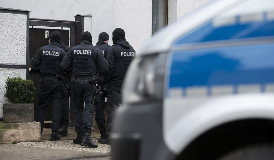 Police officers are standing in front of an apartment building in Erfurt, Germany, Thursday, Jan. 23, 2020. Germany's top security official has announced a ban on the neo-Nazi group 'Combat 18' Deutschland. A spokesman for Interior Minister Horst Seehofer said police were conducting raids early Thursday in six German states. (Jens-Ulrich Koch/dpa via AP)
