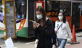 People wear protective face masks on a street in Hong Kong, Friday, Jan 24, 2020. China closed off a city of more than 11 million people Thursday, halting transportation and warning against public gatherings, to try to stop the spread of a deadly new virus that has sickened hundreds and spread to other cities and countries in the Lunar New Year travel rush. (AP Photo/Achmad Ibrahim)