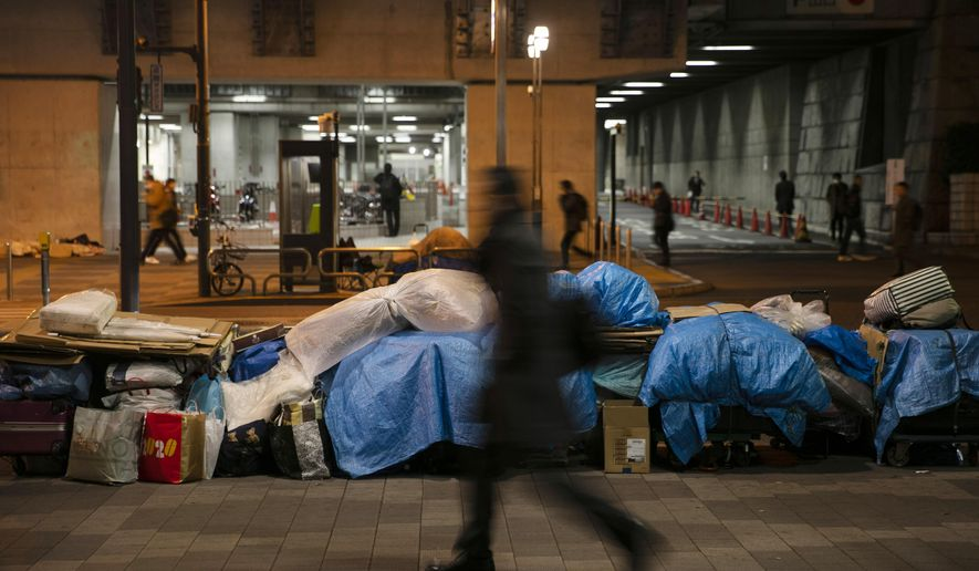 In this Tuesday, Jan. 21, 2020, photo, homeless people's belongings are piled up on a sidewalk, in the Shinjuku district of Tokyo. Like the U.S., Japan has a relatively high poverty rate for a wealthy nation. It also is less generous with social welfare than countries in Europe, and lacks the sorts of private charities prevalent in the U.S. (AP Photo/Jae C. Hong)