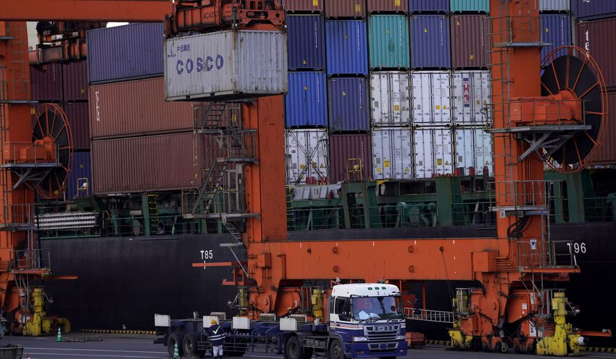 In this Jan. 24, 2018, photo, a worker watches loading and unloading of cargo containers at a port in Tokyo. Japan had the second straight year of red ink in trade for year 2019, hurt by a slowdown of demand in China, according to government data released Thursday, Jan. 23, 2020. (AP Photo/Shizuo Kambayashi)