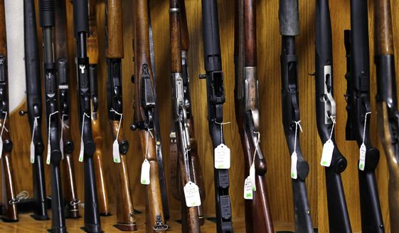 In this Oct. 20, 2017, file photo, rifles are lined up and ready to be auctioned at Johnny's Auction House, where the company handles gun sales for about a half dozen police departments and the Lewis County Sheriff's Office, in Rochester, Wash. (AP Photo/Elaine Thompson, File)