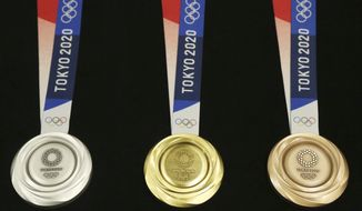 FILE - In this  July 24, 2019, file photo, Tokyo 2020 Olympic medals are unveiled during a One Year to Go Olympic ceremony event in Tokyo. The Tokyo Olympics open exactly six months from Friday, Jan. 24, 2020 and the United States and China are picked to finish 1-2 in the overall medal count and the gold-medal count. That's the easy part in a forecast done by Gracenote Sports about which countries will win the most Olympic medals. Gracenote supplies analysis for leagues around the world and has a solid track record forecasting recent Olympics. (AP Photo/Koji Sasahara, File)