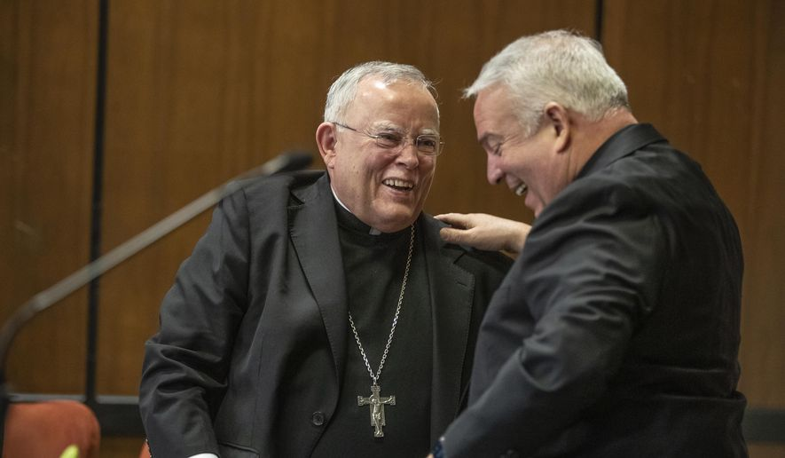 Archbishop Charles J. Chaput, left, and Archbishop-elect Nelson J. Perez, right, share a happy moment after they embraced during the press conference announcing Perez as the Archbishop-elect of Philadelphia on Thursday, January 23, 2020. (Michael Bryant/The Philadelphia Inquirer via AP) ** FILE **