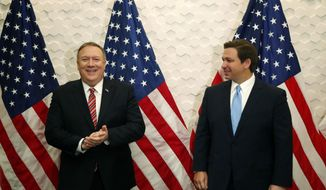Secretary of State Mike Pompeo, left, and Florida Gov. Ron DeSantis pose for a photo before participating in a roundtable discussion with Venezuelan exiles, Thursday, Jan. 23, 2020, in Miami. (AP Photo/Wilfredo Lee)