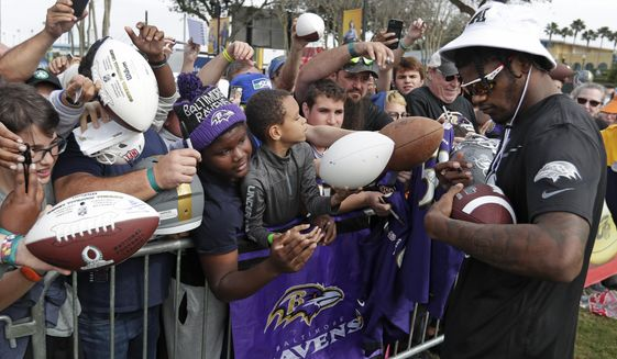 AFC quarterback Lamar Jackson, of the Baltimore Ravens, signs autographs during a practice for the NFL Pro Bowl football game Thursday, Jan. 23, 2020, in Kissimmee, Fla. (AP Photo/John Raoux)