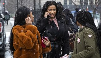 Flanked by supporters, Joycelyn Savage, center, one of R&B singer R. Kelly's girlfriends, walks out of the Cook County Domestic Violence Courthouse, Thursday morning, Jan. 23, 2020, in Chicago. Savage pleaded not guilty to a misdemeanor battery charge for allegedly punching another of the the R&B singer's girlfriends in the face. (Ashlee Rezin Garcia/Chicago Sun-Times via AP)