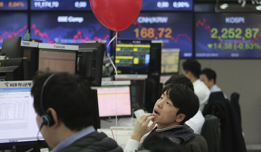 A currency trader watches monitors at the foreign exchange dealing room of the KEB Hana Bank headquarters in Seoul, South Korea, Thursday, Jan. 23, 2020. Asian shares are mostly higher as health authorities around the world move to monitor and contain a deadly virus outbreak in China and keep it from spreading globally. (AP Photo/Ahn Young-joon)