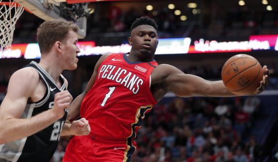 New Orleans Pelicans forward Zion Williamson (1) pulls in a rebound against San Antonio Spurs center Jakob Poeltl (25) in the second half of an NBA basketball game in New Orleans, Wednesday, Jan. 22, 2020. The Spurs won 121-117. (AP Photo/Gerald Herbert) ** FILE **