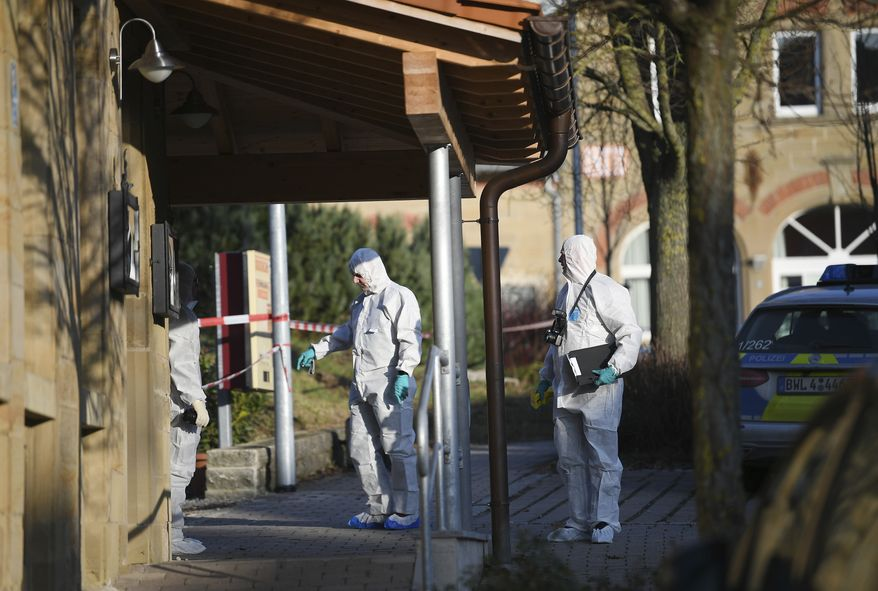 Police at the scene after shots were fired in Rot am See, Germany, Friday, Jan. 24, 2020. Six people have been killed and several were injured in a shooting in the southwestern German town of Rot am See, police said Friday. A suspect has been arrested and no further suspects are believed to be at large, Aalen police said. (Sebastian Gollnow/dpa via AP)