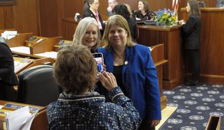 Alaska state Rep. Tammie Wilson, right, poses for a photo with Rep. Andi Story on the House floor as Rep. Gabrielle LeDoux captures the moment on Friday, Jan. 24, 2020, in Juneau, Alaska. Wilson, a North Pole Republican, announced Friday that she is resigning from the House for a policy role focused on children's services with the state. (AP Photo/Becky Bohrer)