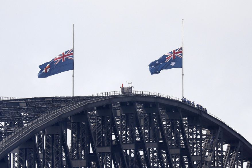 People climbing the Sydney Harbour Bridge stop under flags flying at half-mast as mark of mourning and respect in Sydney, Australia, Friday, Jan. 24, 2020, for three U.S. crew members of an aerial water tanker that crashed Thursday while battling wildfires in Australia. (AP Photo/Rick Rycroft)