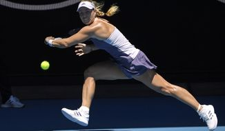 Germany's Angelique Kerber makes a backhand return to Italy's Camila Giorgi during their third round singles match at the Australian Open tennis championship in Melbourne, Australia, Saturday, Jan. 25, 2020. (AP Photo/Andy Brownbill)