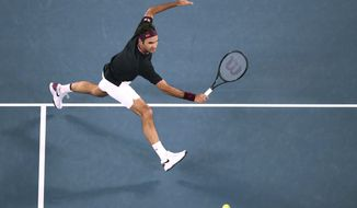 Switzerland's Roger Federer makes a backhand return to Australia's John Millman during their third round singles match at the Australian Open tennis championship in Melbourne, Australia, Friday, Jan. 24, 2020. (AP Photo/Dita Alangkara)