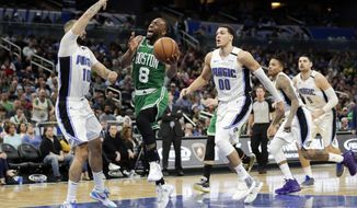 Boston Celtics guard Kemba Walker (8) shoots as he gets between Orlando Magic guard Evan Fournier (10) and forward Aaron Gordon (00) during the second half of an NBA basketball game, Friday, Jan. 24, 2020, in Orlando, Fla. (AP Photo/John Raoux)