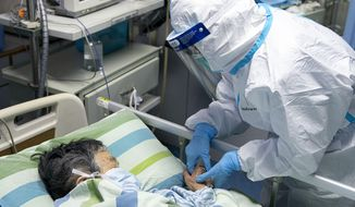 In this Friday, Jan. 24, 2020, photo released by China's Xinhua News Agency, a medical worker attends to a patient in the intensive care unit at Zhongnan Hospital of Wuhan University in Wuhan in central China's Hubei Province. China expanded its lockdown against the deadly new virus to an unprecedented 36 million people and rushed to build a prefabricated, 1,000-bed hospital for victims Friday as the outbreak cast a pall over Lunar New Year, the country's biggest, most festive holiday. (Xiong Qi/Xinhua via AP)