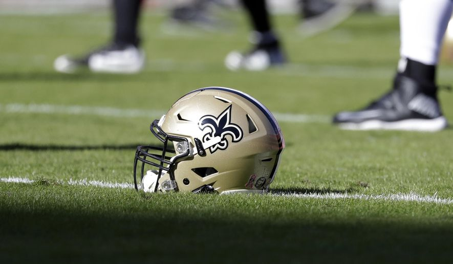 In this Oct. 23, 2016, file photo, a New Orleans Saints helmet rests on the playing field before an NFL football game in Kansas City, Mo. The Saints are going to court to keep the public from seeing hundreds of emails that allegedly show team executives doing public relations damage control for the area's Roman Catholic archdiocese to help it contain the fallout from a burgeoning sexual abuse crisis. (AP Photo/Jeff Roberson, File)  ** FILE **