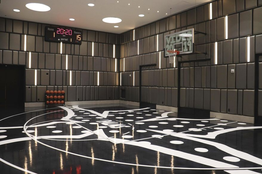 This undated photo shows the regulation-sized half basketball court at the $20,000-per-night Hardwood Suite at The Palms hotel-casino in Las Vegas. The two-story suite also includes a hidden whiskey room, a game room with pool and poker tables, multiple big-screen TVs, a fully-stocked 16-seat bar and a dining table for 10 guests. On this court, the butler keeps score. (Ed Komenda/The Reno Gazette-Journal via AP)