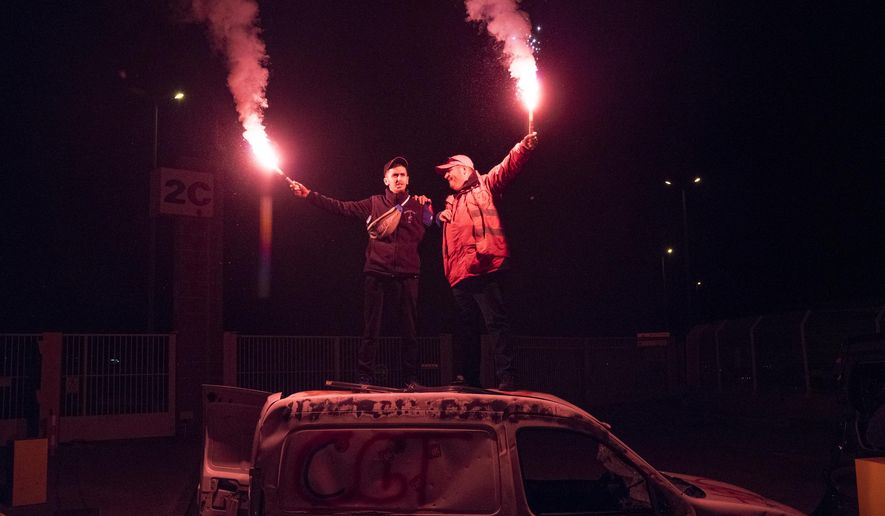 Demonstrators stand on top of a vandalized car with flares during a blockade of the Marseille port in southern France, Thursday, Jan. 23, 2020. Protesters marched in Paris against French President Emmanuel Macron's plans to overhaul the pension system. (AP Photo/Daniel Cole)