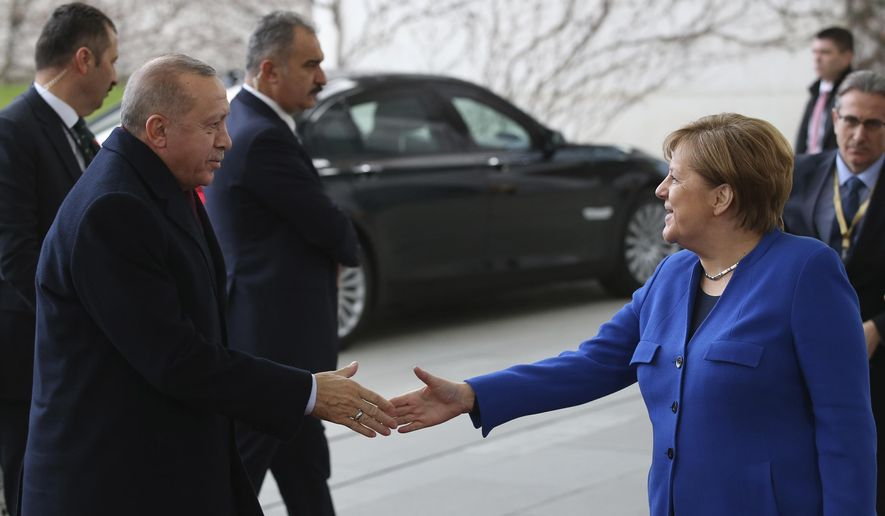 German Chancellor Angela Merkel, right, welcomes Turkish President Recep Tayyip Erdogan before the conference on Libya at the Chancellery in Berlin, Sunday, Jan. 19, 2020. German Chancellor Angela Merkel hosts the one-day conference of world powers in Berlin to discuss efforts to broker peace in Libya.(Turkish Presidency Press Service via AP, Pool)